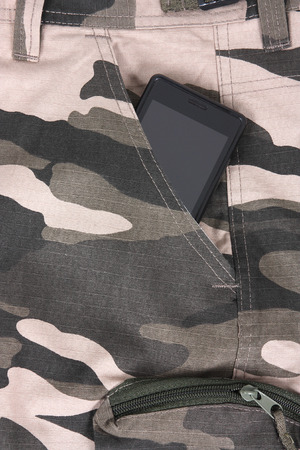 mobile phone in the pocket of camoflauge photo