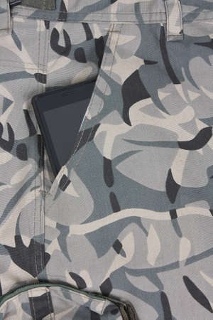 mobile phone in the pocket of pale green camo shorts photo