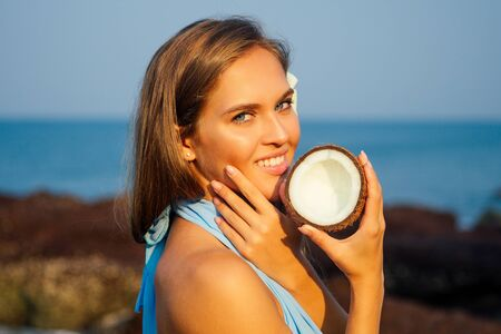 Portrait of beautiful girl close-up snow-white smile,blue eyes and perfectly clean skin holding an open dry coconut near face.female model on the beach happy tropical paradise coco nut oil face care Stock Photo