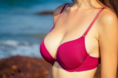 womans chest in red swimsuit closeup against a tropical paradise beach and sea.spf and depilation shugaring epilation concept.