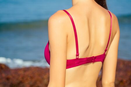 woman's bra back chest in red swimsuit closeup against a tropical paradise beach and sea.spf and depilation shugaring epilation concept. Stockfoto