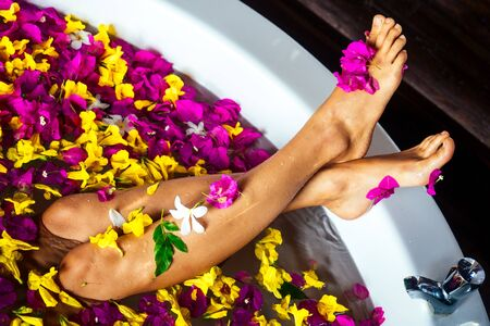 Young woman relaxing in flower bath,organic skin care, luxury spa hotel.legs close up care top view.view from above sexy foot feet girl wellness treathment red,yellow, pink flowers petals in milk bath.