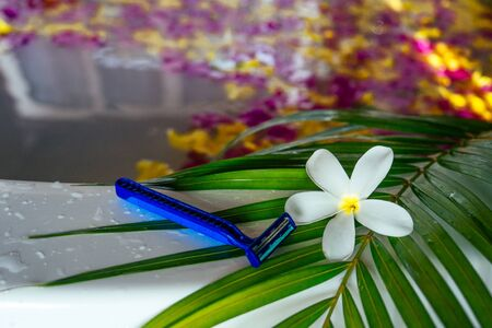 Razor on palm leaf with white tropical flower plumeria on a bath with flower petals sea beach.epilation and depilation removal of unwanted hair from the body spa and female beauty bikini area concept.