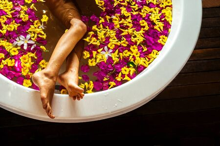 girl shaving her leg with razor in bathroom many petals of tropical flowers.aromatherapy removal of unwanted hairs on the body.naked and tender woman in in bali eco hotel.
