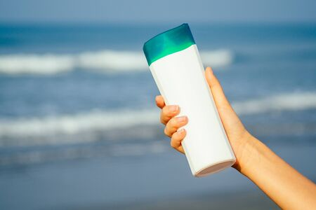 Bottle of sunscreen lotion suncream packaging on the sandy beach sea sky background copy space.oil spa spf summer vacation on tropical paradise copyspace.