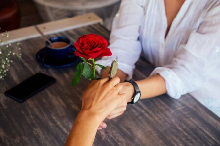 A couple of women spend fun time together in the summer cafe .girl giving a rose to her girlfriend date valentines day.