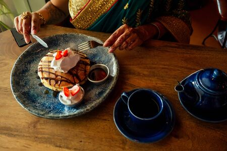 Portrait of a Indian woman in green sari and gold jeweler looking at pancakes with whipped cream and strawberries dessert, eager to eat