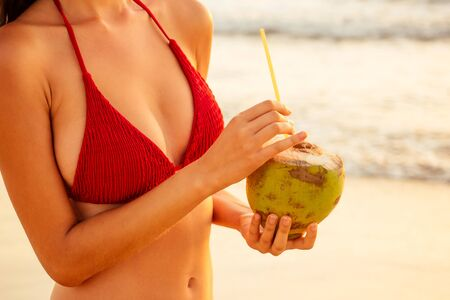 Beautiful sexy young woman posing pretty with coco nut and tube on the tropical beach,big breasts and hips close up summer detox. Zdjęcie Seryjne