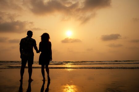 Young couple in love on the beach February 14, St. Valentine's Day sunset Goa India vacation trip .travel new year in a tropical country. freedom concept.