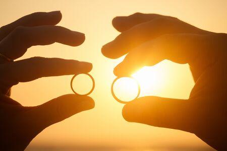 Dos anillos de boda en coral frente al mar al atardecer.