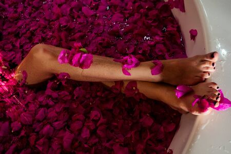 cropped shot of barefoot woman with flowers, candles, colorful sea salt and bath for nails in beauty salon in Bali hotel tropical vacation.depilation epilation shugaring hair removal concept. Zdjęcie Seryjne