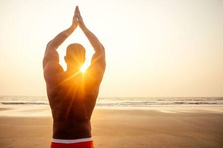 Uomo in piedi nella posa di yoga sulla spiaggia paradisiaca al tramonto sull'oceano. Corpo atletico di Apollo, muscoli