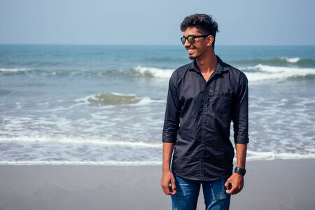 young hindu stylish man posing with sunglasses active beach vacation on semmertime happy Goa India beach. sunscreen spf protection concept.