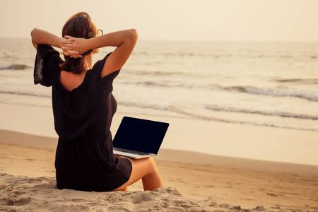 freelance and remote work.business woman in a stylish business summer suit with laptop sitting in the tropical ocean coast palm sand.female student with glasses online training education abroad