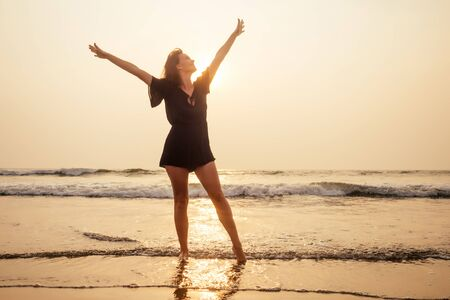 Happy traveller woman in black short dress enjoys her tropical beach vacation at romantic sunset silhouette summer spring time hands up pleasure