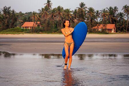 Cooles Surfer-Mädchen, perfekter Körper beim Unterrichten und Üben von Surfkursen. Junge und schöne Frau im Bikini-Badeanzug, die sich vor dem Schwimmen auf dem Surfbrett aufwärmt