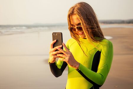 beautiful and young woman in a wetsuit holding a smartphone and photographing the landscape of paradise beach.swimmer girl surfer looking at the phone screen sand, sunset and island