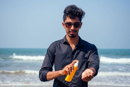 happy young african man on the beach.India model male holding a bottle of sunscreen student teenager on vacation beach goa india