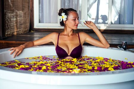 tourist sexy girl taking a bath with tropical flowers on vacation in an exotic summer country.young beautiful woman in round bath tab eco hotel spa salon relaxing aromatherapy and massage womens Day