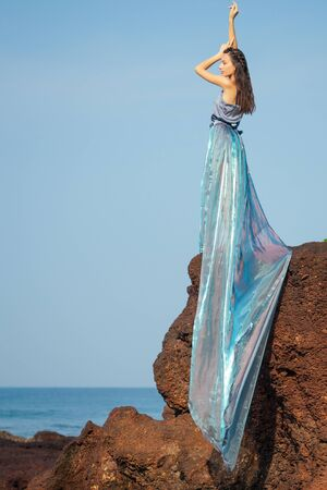 gorgeous style brunette young woman in blue chameleon dress long train standing on a rock near the sea, sand and tropical trees ,big waves beat on a rock.beautiful mermaid lonely melancholy waiting