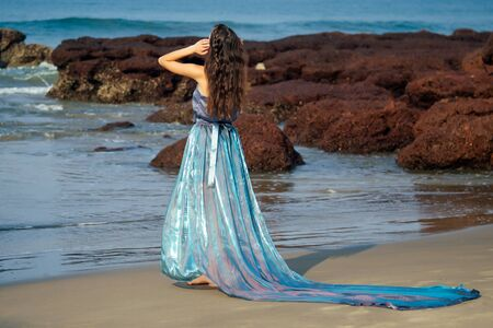 Fashion photo of glamorous brunette woman in a long dress with a train blue chameleon color nymph on the ocean with rocks and waves.