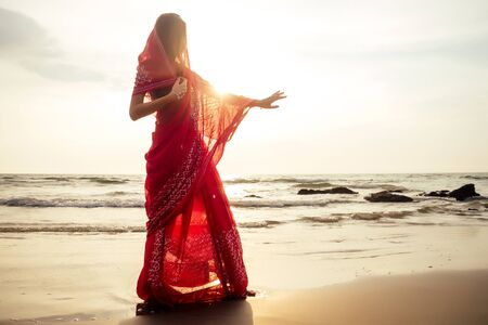 indian female model in vacation on paradise tropical beach by ocean sea. hindu woman with kundan jewelry traditional India costume red wedding sari.asian girl near the rocks shores of Indian Ocean bay