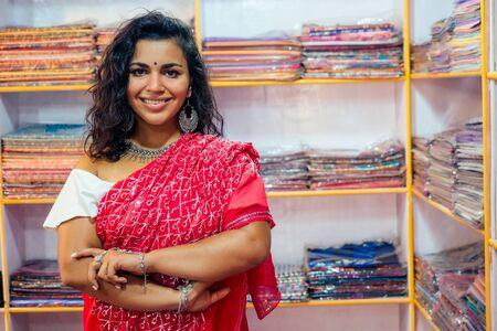 femme d'affaires en rouge sari traditionnel et bijouterie propriétaire de magasin de vêtements cachemire laine de yak châles.vendeuse à goa inde arambol vente shop.designer couturière tailleur fille choisissant le tissu Banque d'images