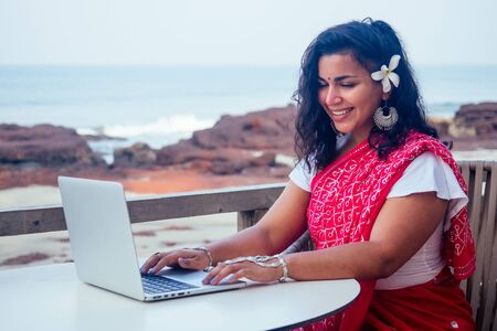 remote working concept dream job.beautiful and young indian woman in red stylish sari ,curly hairstyle,toothy white smile and flower in hair working with a laptop while sitting business woman 版權商用圖片