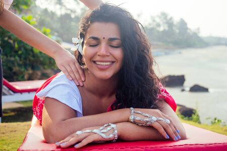 Female beautician doctor with patient make procedure to beautiful indian girl.close up portrait of asian woman closed eyes and white smile wellness head massaging on beach.Face lifting massage in spa