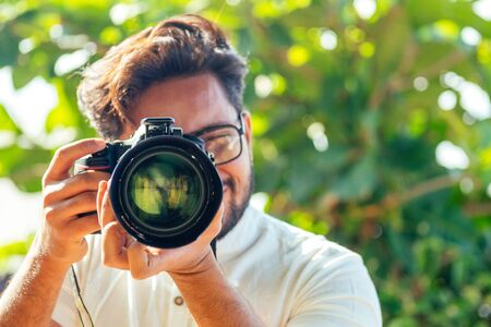 handsome and confident indian man photographer with a large professional camera taking pictures photo shooting on the beach.photo session on summer holiday on the background of green tropical trees
