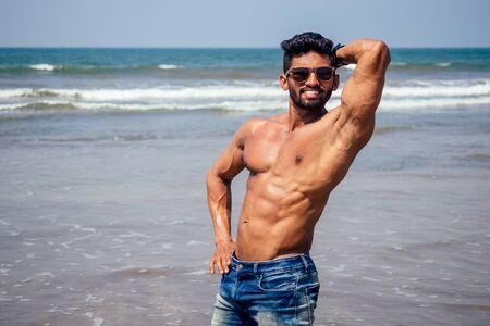 Instructor de calentamiento de hombre negro atlético, musculoso y saludable en topless en la playa.Modelo de moda masculino indio con pantalones cortos de mezclilla, jeans y cuerpo perfecto.Alimentos saludables y vacaciones activas en la playa. Foto de archivo