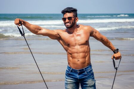 portrait of happy young african man on the beach.Handsome and confident Masculine hard fitness model male body bodybuilder with six pack.India trainer with perfect abs, shoulders,biceps, triceps,chest Imagens