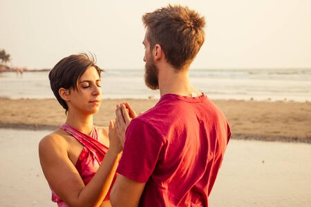 muladhara swadhisthana manipula tantra yoga on the beach man and woman meditates sitting on the sand by the sea at sunset romantic Valentines Day.couple practicing yoga steam 免版税图像