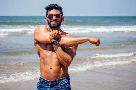 portrait of happy young african man on the beach.Handsome and confident Masculine hard fitness model male body bodybuilder with six pack.India trainer with perfect abs, shoulders,biceps, triceps,chest Stock Photo
