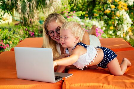 fair-haired one year old female kid looking at a laptop cartoon with mother blonde freelancer surfer on sunbeds resort summer beach.business woman freelancing and daughter relaxing by the sea Stockfoto - 130770689