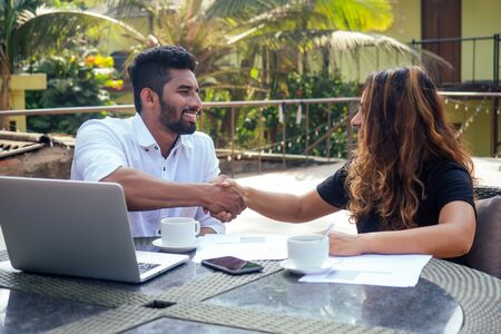 Portrait of happy businesswoman and businessman at summer tropical cafe.freelance and remote work.woman and Arab man couple in love work together on the shore of india ocean Stock Photo