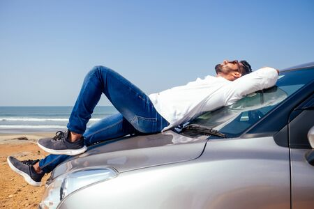 Successful young businessman sunglasses on a beach. Afro man leaning on his car parked in front of ocean on road trip enjoying peace and silence relaxing on nature.Summer vacations and travel concept Imagens