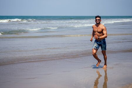 Topless athletic, muscular and healthy black man warm up instructor on the beach.indian male fashion model with denim shorts jeans and perfect body.healthy food and active beach vacation