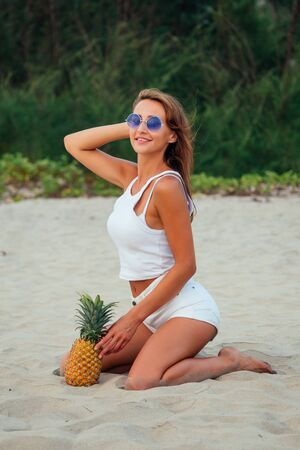 Beautiful woman in a white short topic and shorts with brown hair is holding pineapples on the beach on the background of palm trees.detox and diet Stockfoto