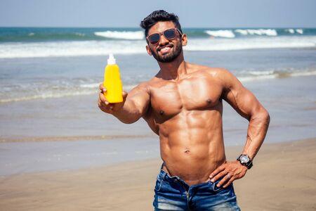 glücklicher junger afrikanischer Mann am Strand. Gutaussehender und selbstbewusster männlicher harter Fitness-Bodybuilder mit Sixpack. Indien-Modell männliche perfekte Bauchmuskeln, Schultern, Bizeps, Trizeps, Brust mit einer Flasche Sonnencreme