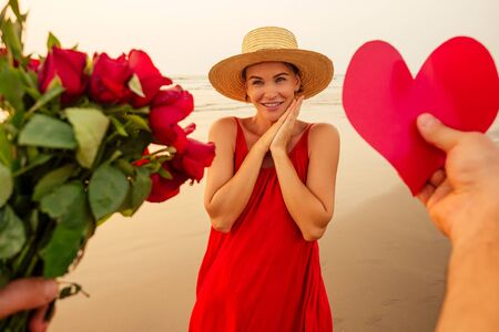 hands of a man giving a heart shaped cardboard valentine and a bouquet of roses to his beloved woman surprised and beautiful woman in red dress and straw hat on the beach by the sea The 14th February