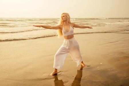 Caucasian woman practicing yoga at seashore warrior pose