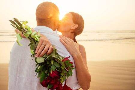 wife and husband happy couple on vacation by the sea.beautiful woman in red dress with a ring on her finger and loving man in a white shirt with a bouquet of roses romantic sunset.Valentines day date