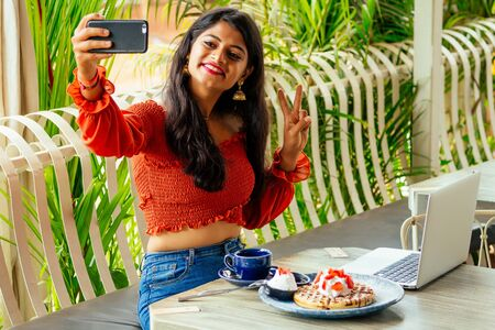 hindu girl at modern outfit sitting at cafe table with mobile phone at hands, making selfie.business woman eating pancakes and working laptop at summer veranda.the university lunch break student