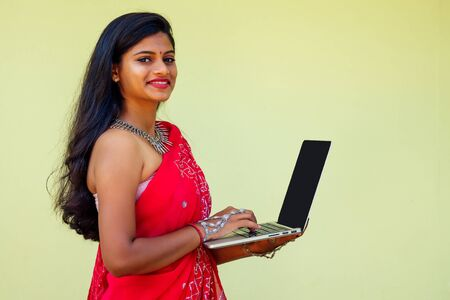 remote working concept dream job. indian business woman in red stylish sari ,curly hairstyle,toothy white smile and flower in hair working with a laptop while sitting in a summer cafe by sea