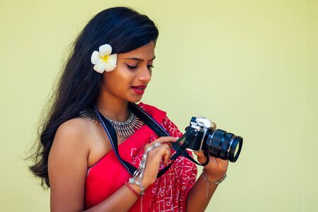 Female India photographer photographing with digital camera on the beach.beautiful indian woman in red traditional sari in the tropical paradise sea taking pictures of the landscape photo shoot
