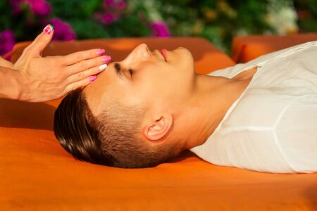 man having oil Ayurveda spa treatment.handsome bearded dark haired male model relaxing on beach.spa and relaxation concept plumeria and coconut Stock Photo