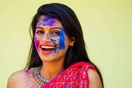 Holi Festival Of Colours. Portrait of happy indian girl in traditional hindu sari on holi color . india woman silver jewelry with powder paint on dress ,colorful pink and blue hair in Goa Kerala Reklamní fotografie