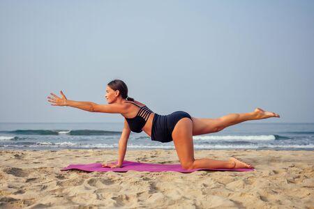 Pregnant woman on the beach doing yoga