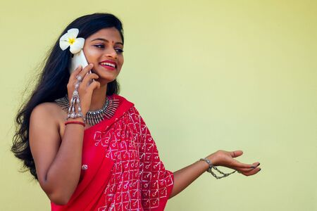 happy india business lady white toothy smile in traditional Indian sari clothes red wedding dress holding a gadget in hand using the phone app in tropic island rocks holiday Indian Bay.girl talking Stock Photo